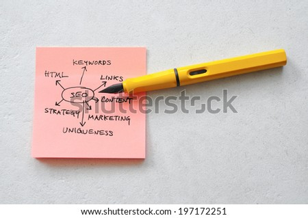 Sticky note with seo plan and pen on table - stock photo