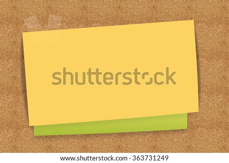 Sticky note yellow and green on cork board - stock photo