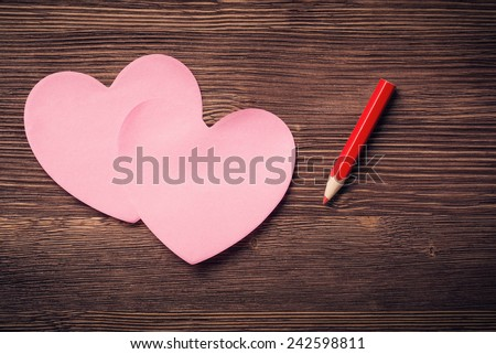 Sticky notes in the form of hearts and red pencil on vintage wooden background - stock photo