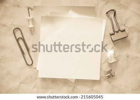 Sticky notes isolated on old paper background with clipping path pins and other office supplies . Above view. - stock photo