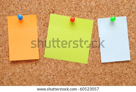 sticky notes over brown cork background - stock photo