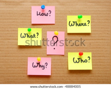 sticky notes with questions over cardboard - stock photo