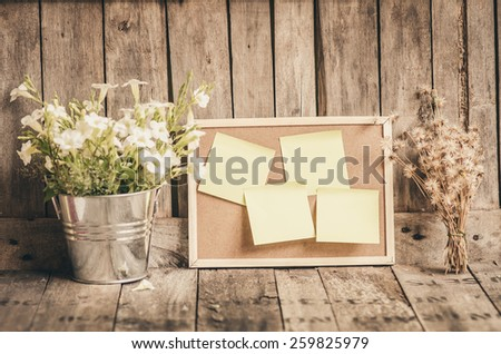 Sticky papers on corkboard with flower pot by wooden background. Vintage photo filter effect. - stock photo