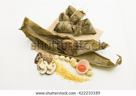 Sticky rice wrapped in bamboo leave for Dragon Boat Festival or Dumpling Festival fall on the 5th day in 5th lunar month. Fillings of glutinous rice, bean, chestnut, duck egg york, mushroom and meat. - stock photo