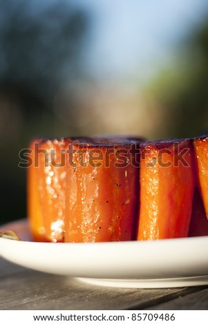 sticky stewed carrots as appetizer outdoors on wooden table
