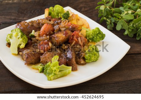 Stifado - a traditional Cypriot dishes, spread in Greece. It consists of a stew with tomatoes, potatoes, broccoli, onions, garlic and spicy spices. Wooden rustic table. Close-up - stock photo