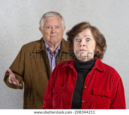 Stiff older woman in front of confused man - stock photo