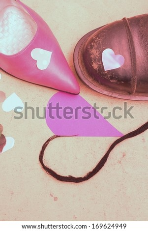 Stiletto heels woman's shoe and a man's boot - opposites attract when it comes to love concept, happy valentine's day - stock photo