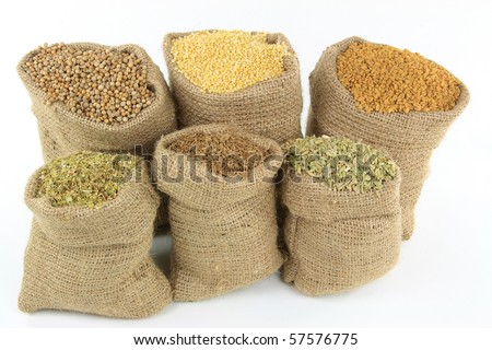 Still image of burlap sacks full with different herbs, seasonings, ingredients, and spices used in preparing food over white background. - stock photo
