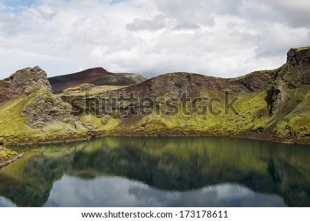Still lake in a crater with reflections on a sunny day, Lakagigar, Iceland - stock photo