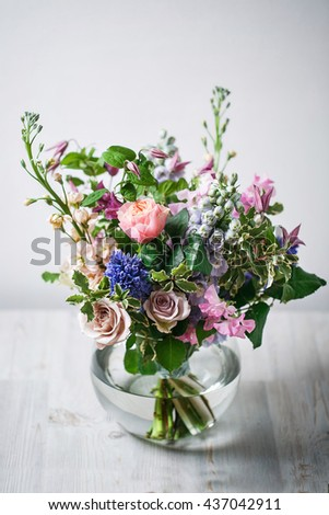 still life. a wooden antique table, glass vase with Mixed bouquet. beautiful flowers - stock photo