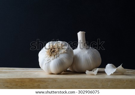 Still life arrangement of two whole, unpeeled garlic bulb heads, with some loose papery skin scattered on wooden chopping board with black background. - stock photo
