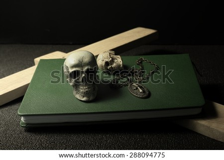 Still life art concept on skulls book cross and necklace - stock photo