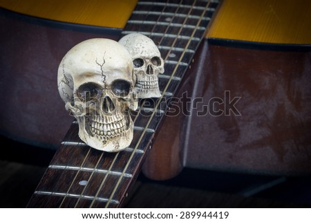 Still life art photography concept with skull and guitar - stock photo