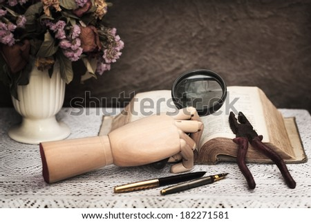 Still life art photography dead academy concept on skull old books vase dry flower wood hand and magnifier - stock photo