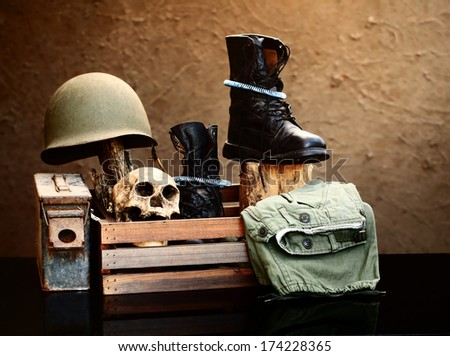 Still life art photography on vintage army concept with helmet jungle boots and metal bullets box pistol and skull - stock photo