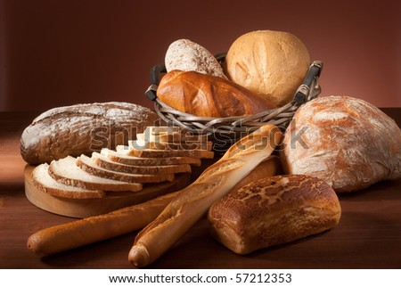 still-life assortment of baked bread over brown background - stock photo
