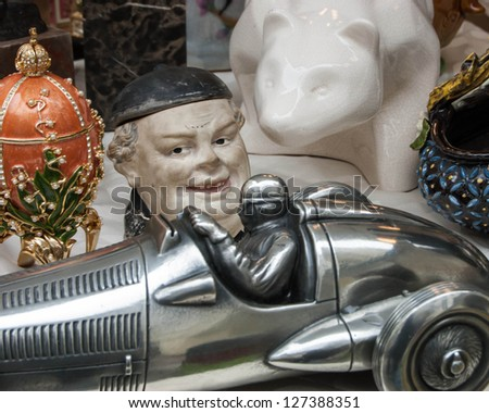 Still life at flea market - toy racing car, laughing man's head, bear and ornate egg - stock photo