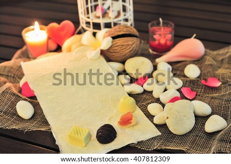 still life blank blurry paper note to fill text under candle light with flower over decorated background for love theme and valentine concept. selective focus. - stock photo