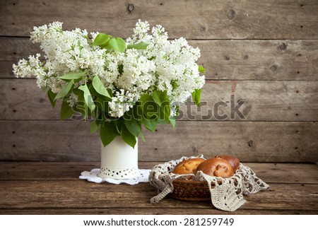 Still life. Bouquet of white lilacs in a vase and patties with apples on a wooden table. Rustic style and selective focus. Toned. - stock photo