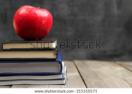 Still life, business, education concept. Notebook stack and apple on a wooden table with chalk and chalkboard. Selective focus, copy space, school background - stock photo