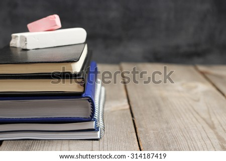 Still life, business, education concept. Notebook stack on a wooden table with chalk and chalkboard. Selective focus, copy space, school background - stock photo