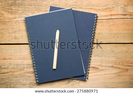Still life, business, education concept. Notepad and pencil on a wooden table. Selective focus, copy space background, top view - stock photo