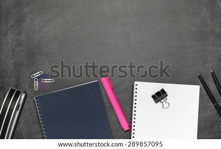 Still life, business, education concept. Office supplies, notepad, diary, marker, stapler, pens and pencils on a chalkboard. Selective focus, copy space background, top view - stock photo