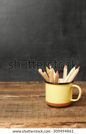 Still life, business, education concept. Pencils in a mug on a wooden table and chalkboard. Selective focus, copy space, school background - stock photo