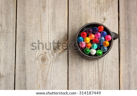 Still life, business, education concept. School, office supplies, crayons (pencils) in a mug on a wooden table. Selective focus, top view, copy space background - stock photo
