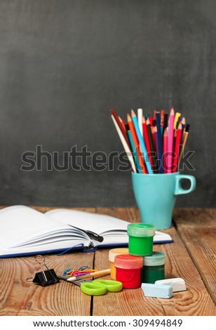 Still life, business, education concept. School supplies and open notebook on a wooden table with chalkboard. Selective focus, copy space, school background - stock photo