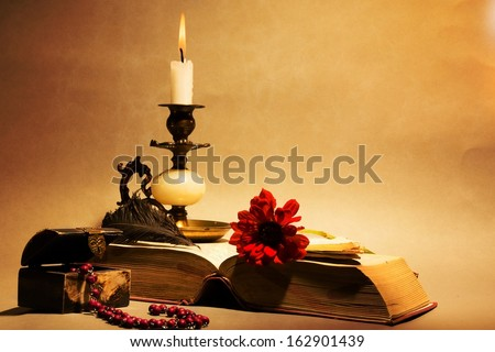 Still life. Candle, old book, feather, pen, small chest on orange background. - stock photo