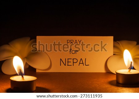 still life candle with flower and note pray for Nepal. background. candle flame at night.Abstract background background for pray for Nepal earthquake. - stock photo