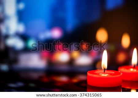 still life candle with reflection over city night light bokeh background. - stock photo
