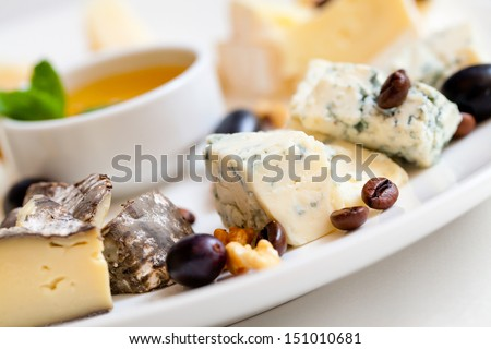 Still-life cheese platter with nuts and grapes - stock photo