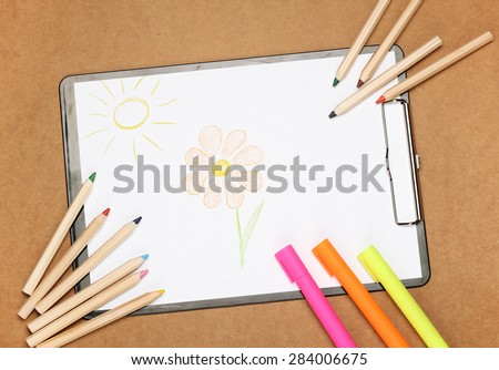 Still life, children, school, education concept. Drawing flower and sun with stationery, markers and pencils on a table. Selective focus, copy space background, top view - stock photo
