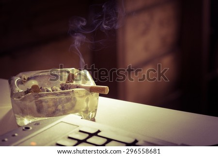 Still life cigarette and glass ashtray. Some man like smoking in work time for make idea. - stock photo