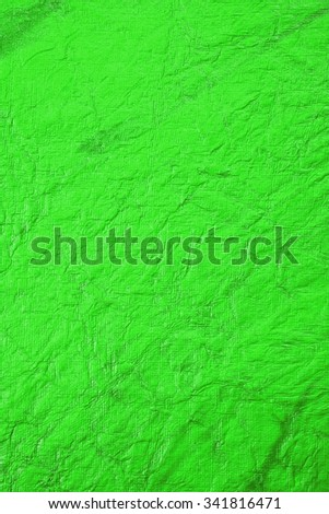 Still life close up detail of a bright green rough grungy wrinkled piece of paper with lines and texture. Plain full frame Christmas background with textured detail. Monotone colorful blank page. - stock photo