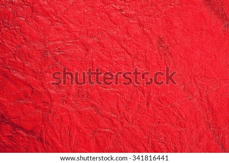Still life close up detail of a bright intense red rough grungy and wrinkled piece of paper with lines texture. Plain full frame Christmas background with textured detail. Monotone color blank page. - stock photo