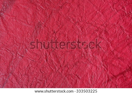 Still life close up detail of bright vivid intense red rough grungy and wrinkled piece of paper with lines texture. Plain full frame background with scratches detail. Monotone colorful blank page. - stock photo