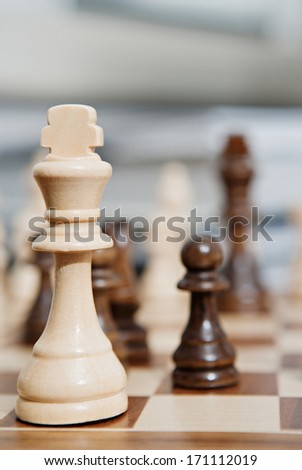 Still life close up detail view of a king chess wooden piece on a chess board while a strategic game is being played. Interior game playing. - stock photo