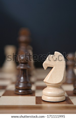 Still life close up detail view of a knight chess wooden piece on a chess board while a strategic game is being played. Interior professional strategy game playing. - stock photo