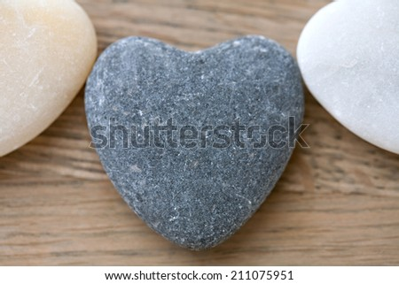 Still life close up of three heart shaped natural stones laying next to each other on a wooden texture background, in a health spa interior. Nature elements and energy zen relaxing treatments. - stock photo