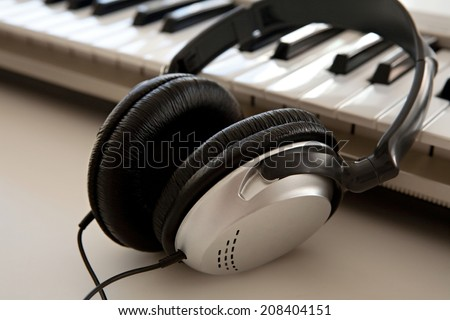 Still life close up of two electronic music and sound devices laying together on a white desk in a recording studio, interior. Detail view of a pair of headphones and a keyboard, technology. - stock photo