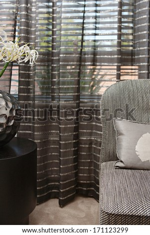 Still life close up view of an elegant sofa in a luxury home living room with curtains and different natural fabrics, cushions and textures. Hotel interior suite detail with fresh flowers. - stock photo