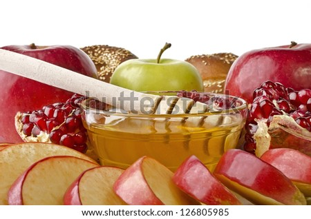 Still life closeup - challah, apples, pomegranate and bowl of honey, isolated over white. Illustration of Rosh Hashanah (jewish new year) or Savior of the Apple Feast Day