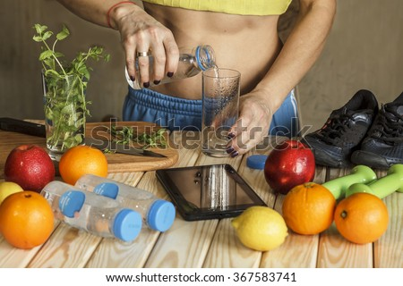 Still life, closeup.  Girl with a naked torso pours clean water into a glass. Fresh fruits, herbs, Tablet PC, running shoes, dumbbell on the wooden table. Concept: healthy lifestyle. Vintage