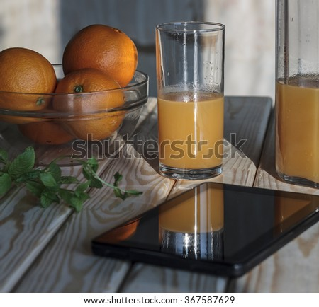 Still life, closeup.  juice into the glass.   juice in jug. Fresh fruits, herbs, Tablet PC, running shoes, dumbbell on the wooden table. Concept: healthy lifestyle. Vintage