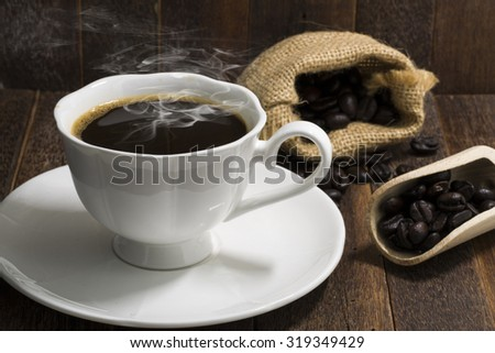 Still life coffee cup on wood background with beans in scoop and sack - stock photo