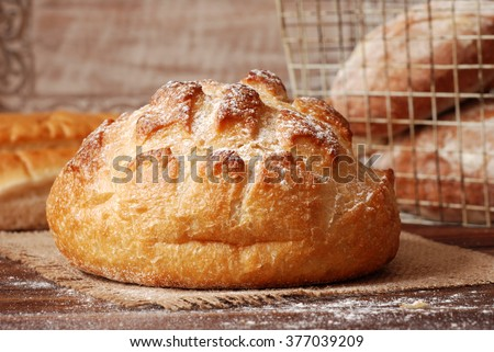 Still-life composition of freshly baked homemade bread on burlap over flour-dusted wood table.  Rustic background includes wire basket and distressed wood.  Closeup;   natural light; and shallow dof.